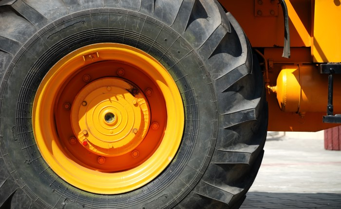 A large industrial tire on a yellow rim and vehicle